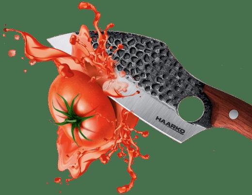 Knife slicing tomato